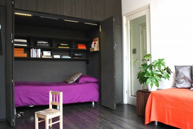 334905-R3L8T8D-650-space-saver-beds-with-purple-bedding-and-built-in-bookshelves-also-cabinets-with-dark-wood-flooring-and-indoor-plant-plus-day-bed-bedding 21 Ide Brilliant Untuk Membuat Kamar Kecil Kamu Menjadi Lebih Menyenangkan